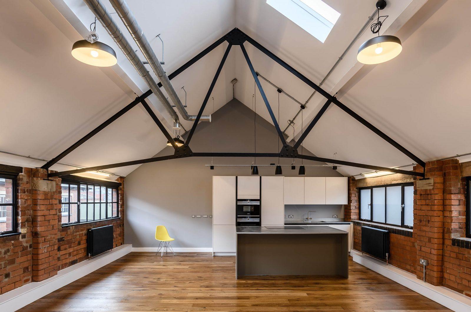 LIV Projekt open plan modern white kitchen with exposed brick walls