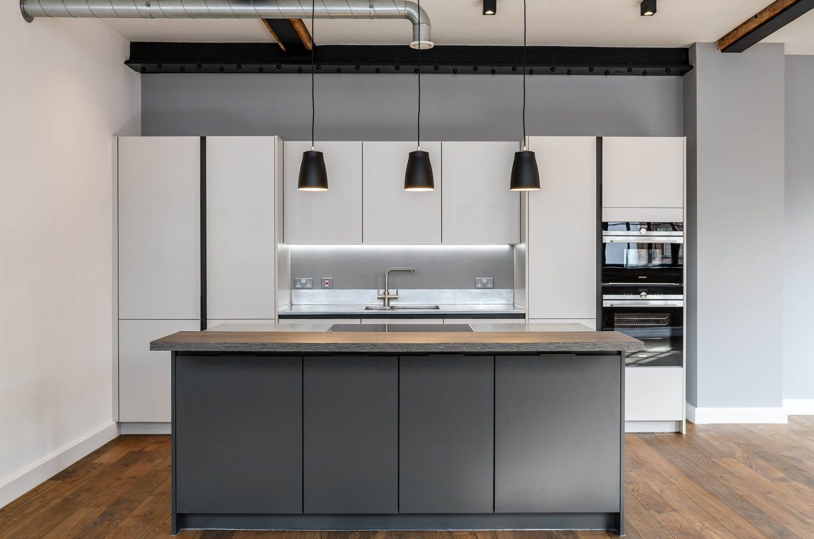 LIV Projekt modern black and grey kitchen with 3 black pendant lights in an industrial style room