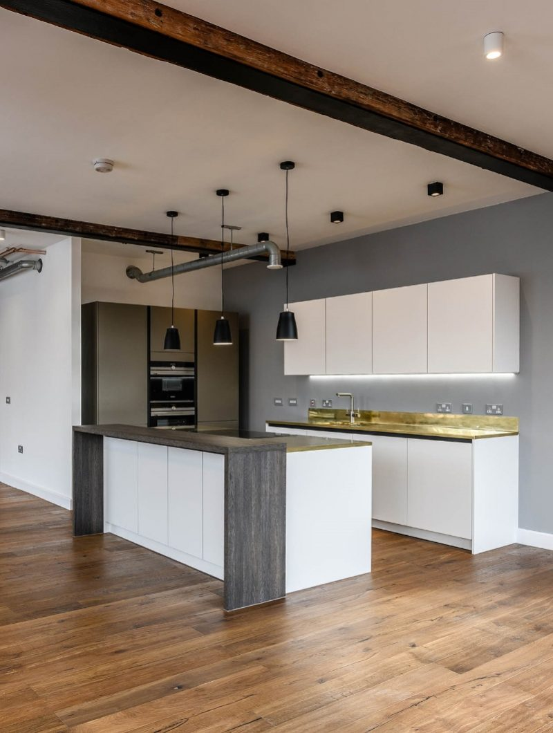 Live Projekt industrial apartment kitchen with modern white cabinets and gold worktop