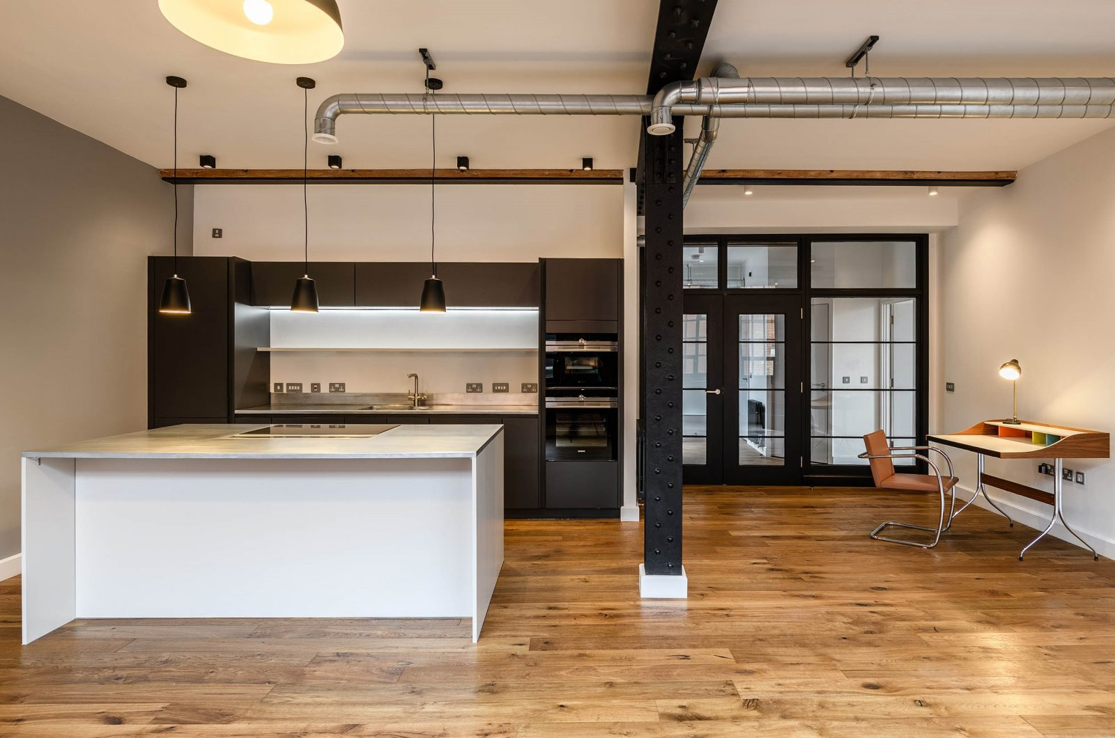 LIV Projekt modern black kitchen with a large island below 3 black pendant lights in an industrial style room