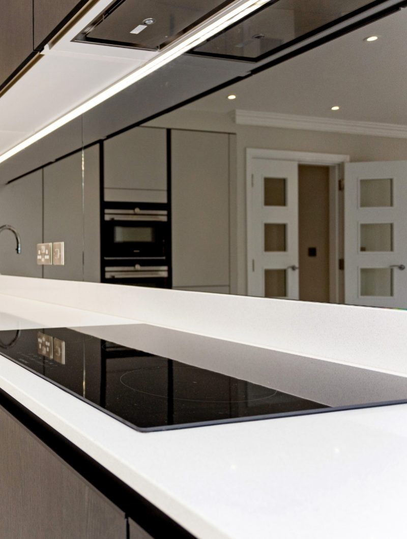 Tudor place project kitchen with white worktops and reflective backsplash