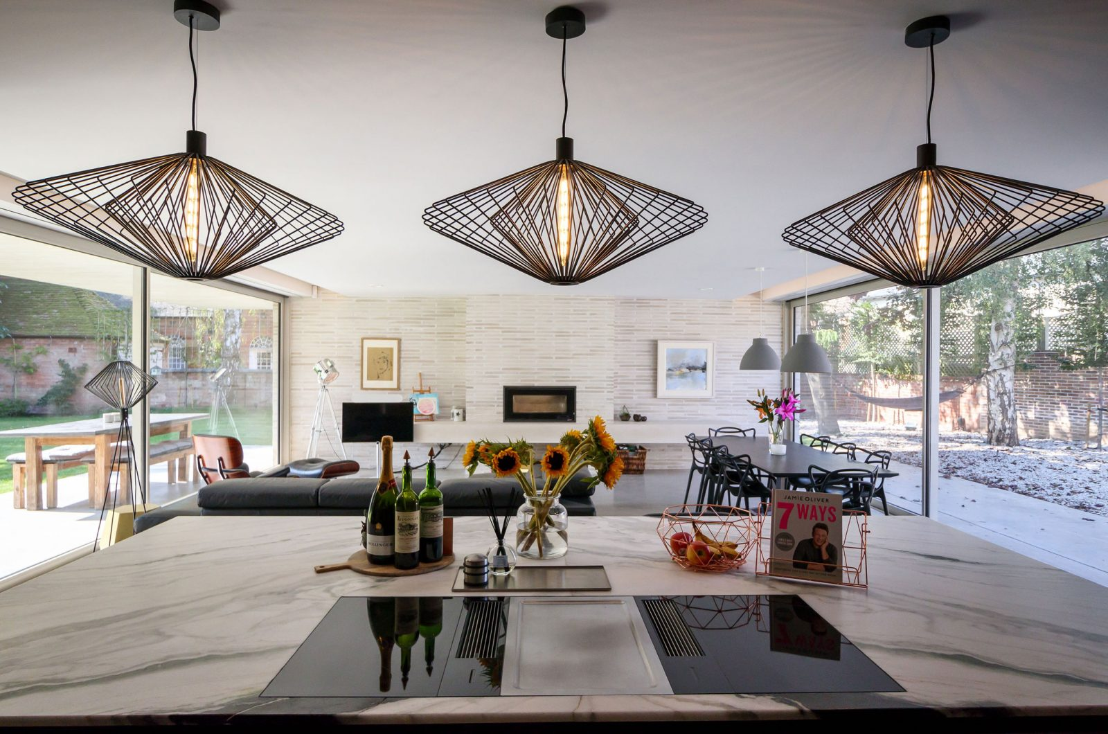 Studio Spicer project looking onto an open plan Kitchen with 3 pendant lights