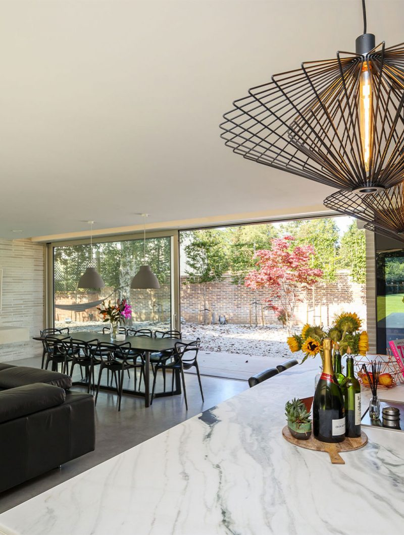 Studio Spicer project open plan kitchen with modern dining table and bifolding doors to the garden