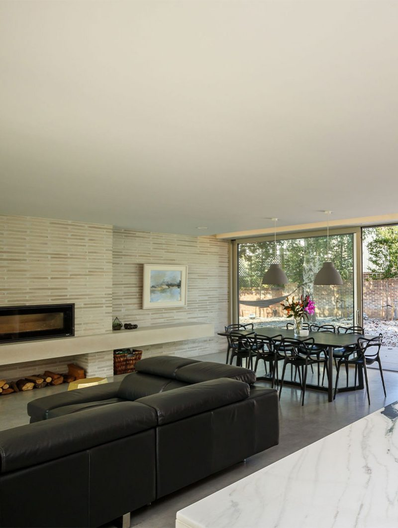 Studio Spicer project open plan living space with a leather sofa next to a fireplace that spans the width of the room